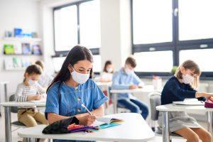 Schulkinder mit Hygienemaske im Klassenzimmer